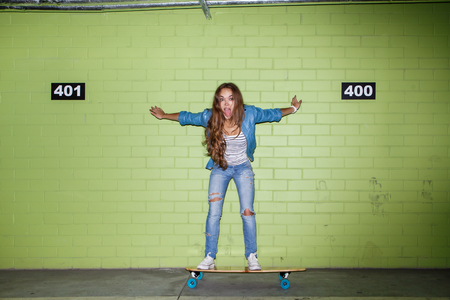 young beautiful long-haired brunette lady in blue jeans stand on wooden longboard skateboard and touch green brick wall Stock Photo