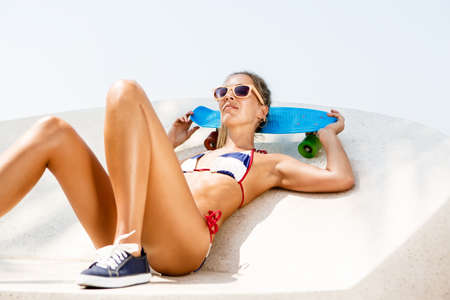 Beautiful sexy woman in blue and white striped bikini and sunglasses lying on her penny board longboard with multi colored wheels while resting in the skate park