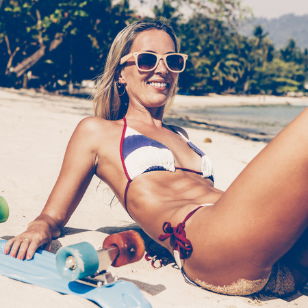 Beautiful lady in blue and white striped bikini and sunglasses laughing while lying on sandy beach near her penny board