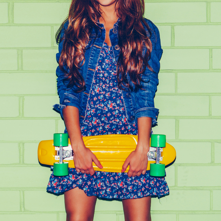 young happy beautiful long-haired brunette girl in blue dress stand with yellow plastic penny board skateboard near the green brick wall and looking into the camera