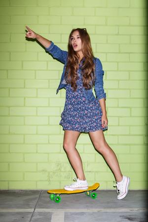 belle jeune balade à poil long dame plastique jaune planche à roulettes penny shortboard et montrer quelque chose avec sa main levée, près du mur de briques vertes