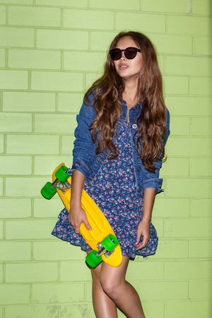 young beautiful long-haired brunette lady in blue dress and sunglasses stand with yellow plastic penny board skateboard near the green brick wall