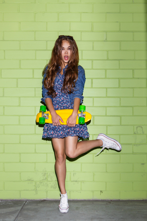 young beautiful long-haired lady with yellow plastic penny board skateboard jump on one leg near the green brick wall