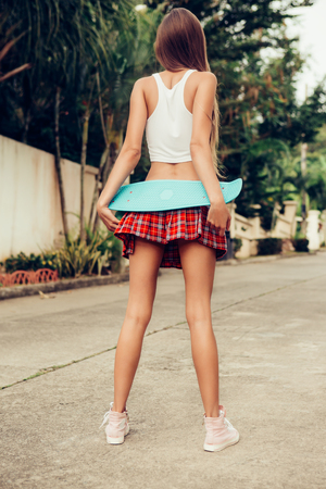 Sexy young lady hold her blue penny skateboard longboard on a sexy red tartan mini skirt while stands on a tropical street. Outdoor lifestyle picture on a sunny summer day. Stock Photo