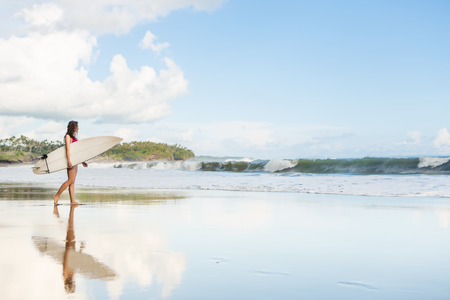 wind surfing: beautiful young lady with long hair in pink bikini with surfboard going to he ocean at surf spot Stock Photo