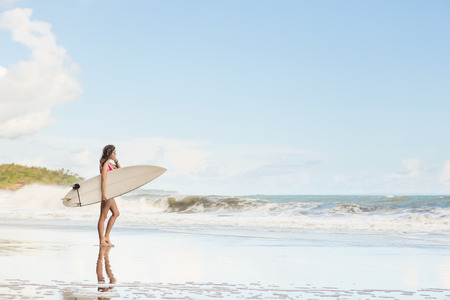 beautiful young woman with long hair in pink swimsuit with surfboard wait on surf spot at sea beach