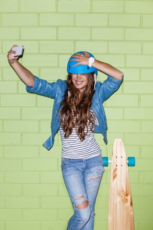 sexual girl: young beautiful long-haired brunette girl in blue helmet with wooden longboard skateboard taking a selfie self portrait of herself coquettishly posing at the camera on her smartphone digital camera near the green brick wall