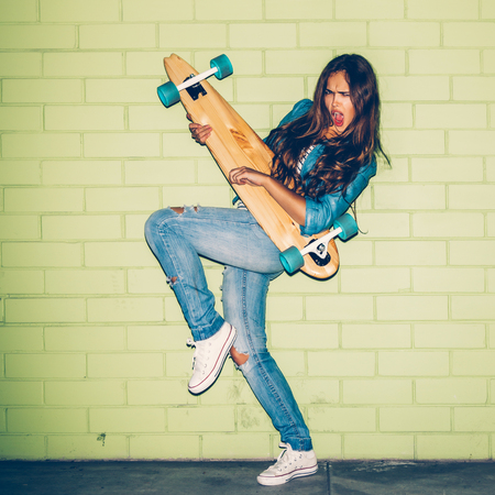 longboard: beautiful long-haired lady emotionally play air guitar with wooden longboard skateboard near the green brick wall Stock Photo