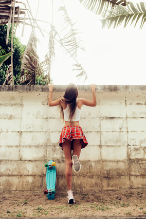 Sporty young woman with sexy ass in a red tartan mini skirt with blue penny skateboard trying to climb over the fence of a tropical garden. Outdoor lifestyle picture on a sunny summer day.