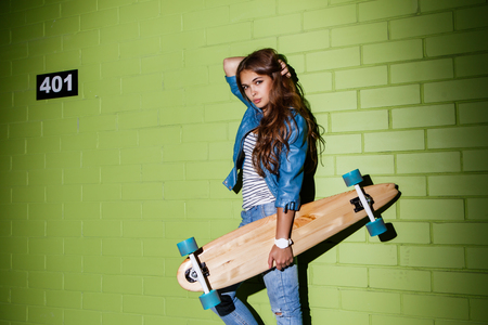 corrects: young beautiful long-haired lady with wooden longboard corrects her hairs near the green brick wall