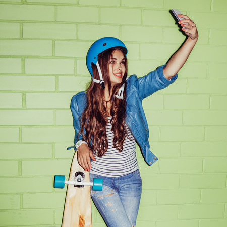 young beautiful long-haired brunette woman in blue helmet with wooden longboard skateboard taking a selfie self portrait of herself looking at the camera on her smartphone digital camera near the green brick wall Stock Photo