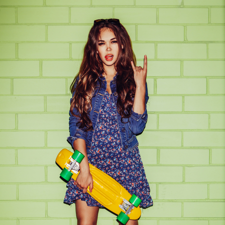 sexual activities: young beautiful long-haired woman with yellow plastic penny shortboard skateboard show sign of the horns near the green brick wall