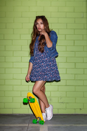 young happy beautiful long-haired brunette woman in blue dress and sunglasses with yellow plastic penny board skateboard near the green brick wall plays wit her lips