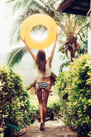 woman ass: Athletic young woman with sexy sporty ass in a striped bikini with yellow inflatable swimming ring walking on stone steps in a tropical garden. Outdoor lifestyle picture on a sunny summer day.