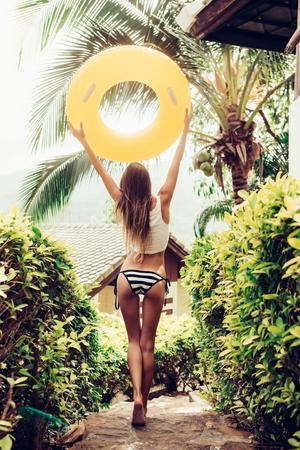 culo: Mujer joven atlético con culo deportivo sexy en un bikini a rayas con amarillo anillo de natación inflable caminando en escalones de piedra en un jardín tropical. Imagen de estilo de vida al aire libre en un día soleado de verano. Foto de archivo