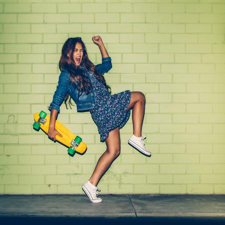 diversion: feliz joven hermosa niña morena de pelo largo en el vestido azul que se divierte con el tablero del penique plástico amarillo patineta delante de la pared de ladrillo verde