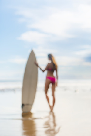 attractive girl: blurry silhouette of a beautiful girl with long hair in a pink swimsuit with surfboard on the beach. a picture from a dream. picture is not in focus.