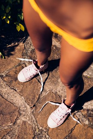 unleashed: Beautiful athletic young girl in a yellow knitted bikini looks at her converse sneakers with unleashed shoelaces on the stone path in a tropical garden. Outdoor lifestyle on a hot sunny summer day.