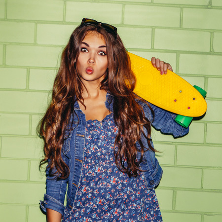 young beautiful long-haired brunette girl with yellow plastic shortboard penny skateboard coquettishly sending an air kiss near the green brick wall Фото со стока