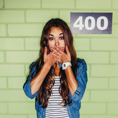 beautiful long-haired young woman stays surprised near the green brick wall