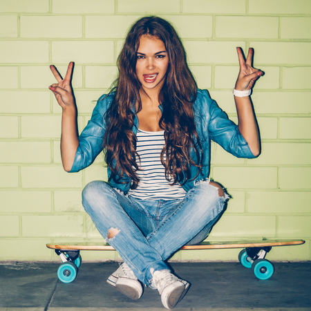skateboard: young beautiful long-haired brunette lady sits on her wooden longboard skateboard and show victory signs near the green brick wall