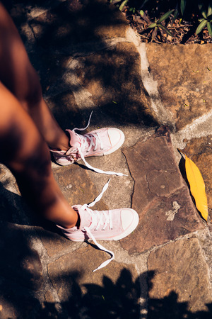 untied: Beautiful athletic young woman in a yellow knitted bikini looks at her sneakers with untied shoelaces on the stone path in a tropical garden. Outdoor lifestyle on a hot sunny summer day.