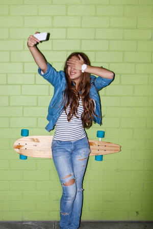 young beautiful long-haired brunette girl with wooden longboard skateboard taking a selfie self portrait of herself coquette at the camera on her smartphone digital camera near the green brick wall