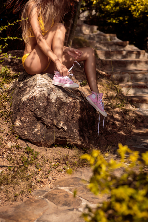 converse: Athletic skinny young girl in a yellow swimsuit tying laces in her pink converse sneakers while sitting on a stone near steps in a tropical garden. Outdoor lifestyle picture on a sunny summer day. Stock Photo