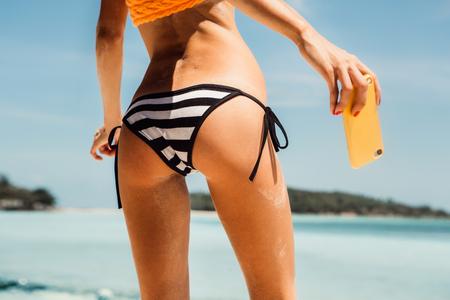 junge nackte m�dchen: Sportliche junge sch�ne Dame, die ein selfie Selbstportr�t ihrer fit Hintern in einem sexy stripped Bikini an der Kamera auf ihrem Smartphone Digitalkamera. Outdoor-Lifestyle-Bild an einem hei�en sonnigen Sommertag.