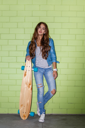 beautiful long-haired girl with wooden longboard skateboard stand near the green brick wall Stock Photo