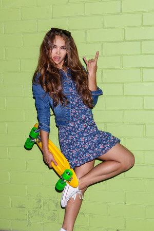 young beautiful long-haired girl with yellow plastic penny shortboard skateboard show sign of the horns near the green brick wall
