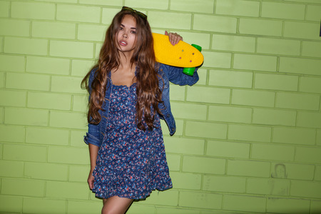 young happy beautiful long-haired brunette girl in blue dress with yellow plastic penny board skateboard in front of the green brick wall