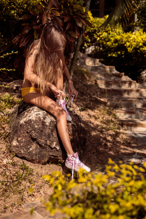 converse: Skinny sexy young woman in a yellow swimsuit tying shoelaces in her pink converse sneakers while sitting on a stone near steps in a tropical garden. Outdoor lifestyle picture on a sunny summer day.