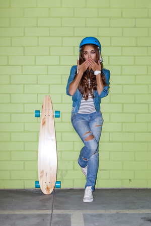 young beautiful long-haired brunette girl in blue helmet with wooden longboard skateboard coquettishly sending an air kiss near the green brick wall