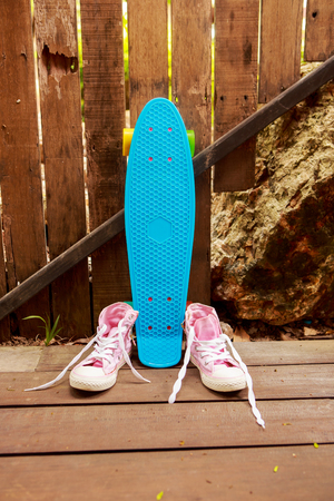 converse: Pink converse sneakers with untied laces on a wooden floor near blue penny skate board longboard with multi color wheels. Urban hipster outfit