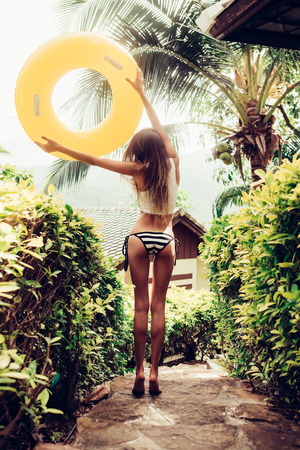 Skinny young lady with erotic sporty ass in a striped bikini with yellow inflatable swimming ring walking on stone steps in a tropical garden. Outdoor lifestyle picture on a sunny summer day.
