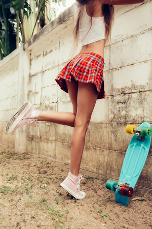 Close up of a young lady with sporty butt in a red tartan mini skirt with blue penny skateboard trying to climb over the fence of a tropical garden. Outdoor lifestyle picture on a sunny summer day.