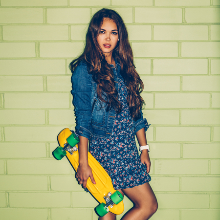 sexual activities: young beautiful long-haired brunette woman in blue dress stand with yellow plastic penny board skateboard near the green brick wall and looking into the camera Stock Photo