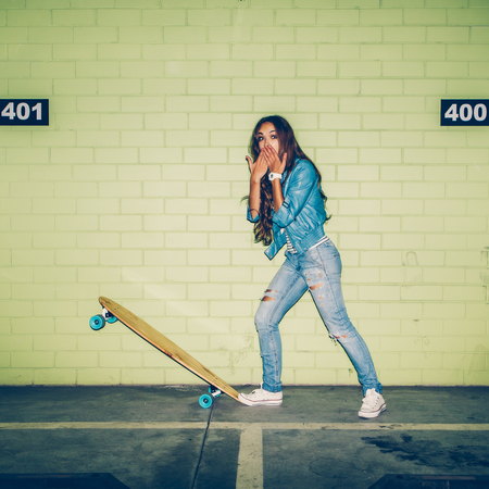 sexual activities: young beautiful long-haired brunette lady with wooden longboard skateboard coquettishly sending an air kiss near the green brick wall