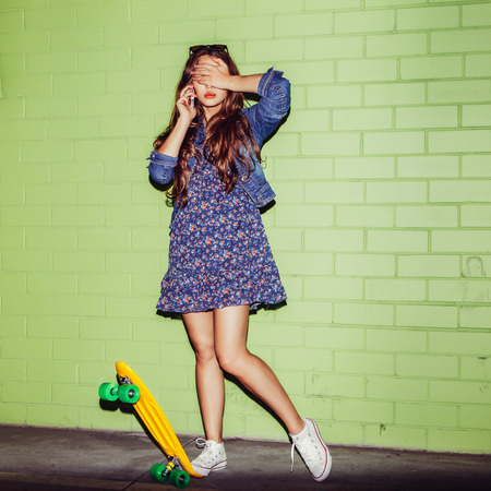 young happy beautiful long-haired brunette lady in blue dress with yellow plastic penny board skateboard near the green brick wall talking by the smartphone phone and close her eyes Фото со стока