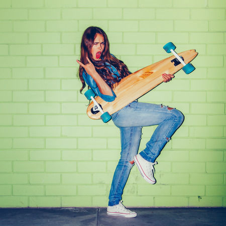 rowdy: beautiful long-haired woman show sign of the horns while play air guitar with wooden longboard skateboard near the green brick wall