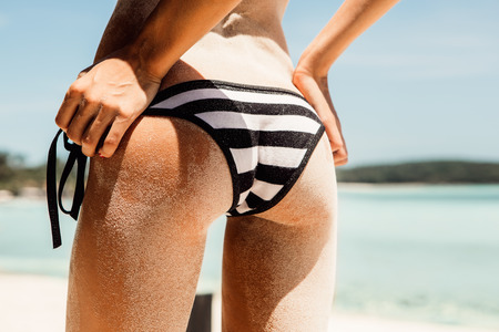 nude butt: Sandy butt of a young beautiful sporty woman in sexy striped black and white bikini panties on the tropical sea shore background. Outdoor lifestyle picture on a hot sunny summer day. Stock Photo