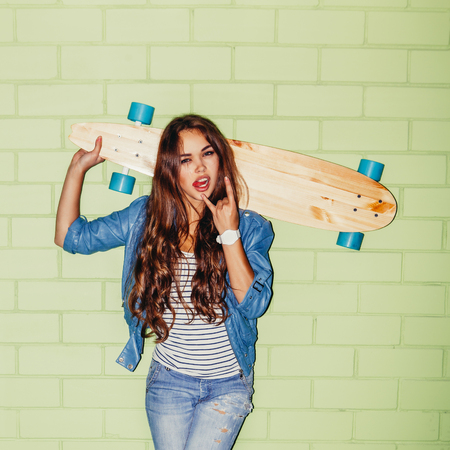 rowdy: beautiful long-haired girl with wooden longboard show sign of the horns near the green brick wall Stock Photo