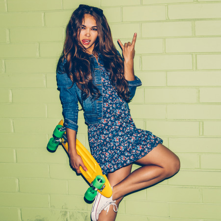 rowdy: young beautiful long-haired girl with yellow plastic penny shortboard skateboard show sign of the horns near the green brick wall