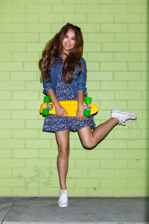 young beautiful long-haired girl with yellow plastic penny board skateboard jumping on one leg against the green brick wall Stock Photo