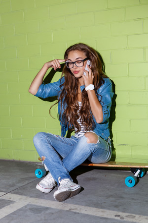 lady on phone: young beautiful long-haired brunette lady sits on her wooden longboard skateboard and touch her head while emotionally talking on the smartphone phone near the green brick wall