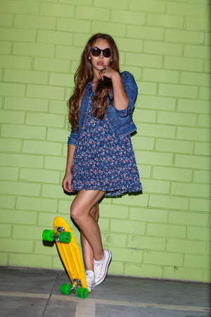 sexual activities: young happy beautiful long-haired brunette lady in blue dress with yellow plastic penny board skateboard near the green brick wall plays wit her lips