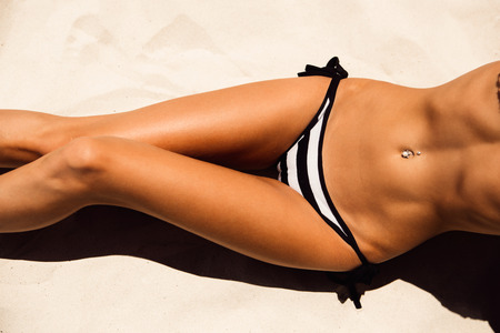 erotic women: Skinny young beautiful woman in a striped black and white bikini sunbathing on the soft sandy sea shore. Outdoor lifestyle picture on a hot sunny summer day. Stock Photo
