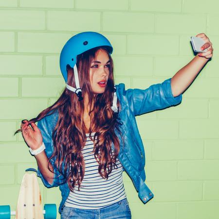 hermosa mujer morena de pelo largo en el casco azul que toma un retrato de sí misma autofoto auto presenta con el rizo de pelo rizo a la cámara en su teléfono inteligente cámara digital cerca de la pared de ladrillo verde