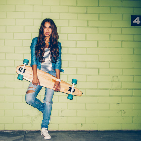 sexual activities: young beautiful long-haired brunette girl in blue jeans stand with wooden longboard skateboard near the green brick wall and flirts with camera